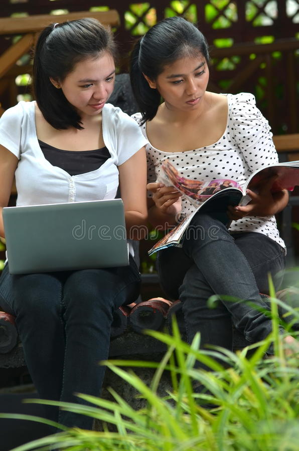 Girls Activity and Friendship. Two pretty girls (southeast asian) enjoying themselves as they studying, learning and sharing information they found on a book/ stock photos