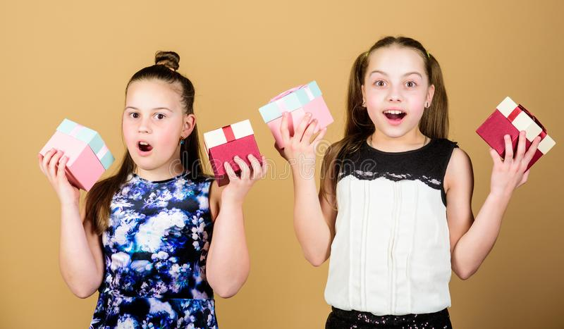 Girls adorable celebrate birthday. Kids happy loves birthday gifts. Shopping and holidays. Sisters enjoy presents. Children hold gift boxes beige background stock image