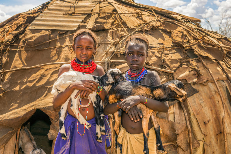 Girls from the African tribe Daasanach holding goats. OMO VALLEY, ETHIOPIA - MAY 6, 2015 : Two girls from the African tribe Daasanach holding goats in front of stock photo