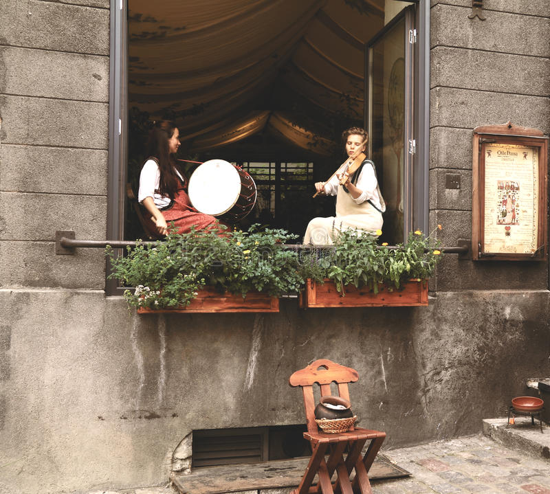Girls in ancient Estonian clothes play on musical instruments royalty free stock photography
