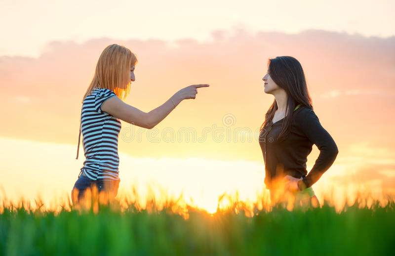 Girls arguing pointing a finger and ignoring. Two girls arguing pointing a finger and ignoring royalty free stock photography