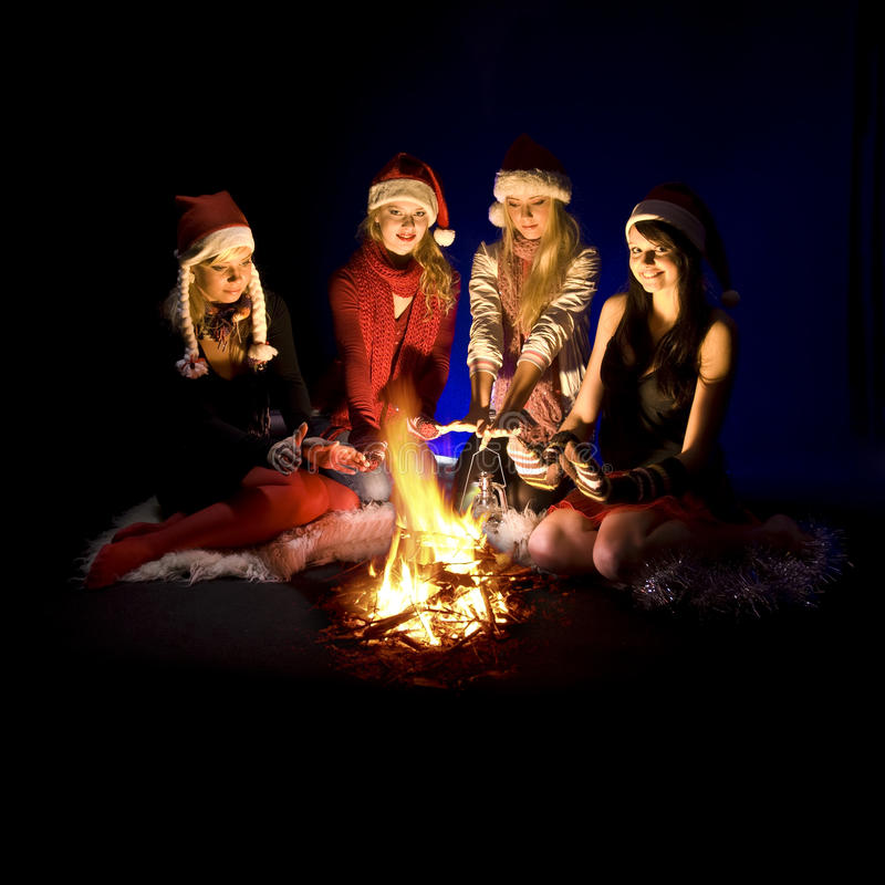 Girls around campfire. Group of four teenage girls in Santa hats sit around a campfire. Isolated against a black background stock image