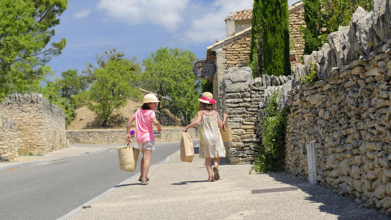 Girls arriving from market in Provence. Two girls arriving from the market in Provence, France stock photography