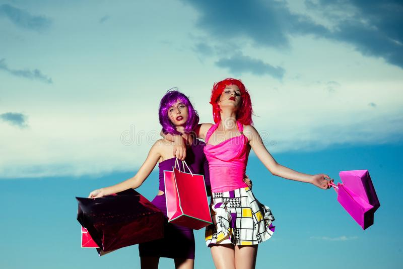 Girls with artificial hair with colorful shopping bag. royalty free stock image