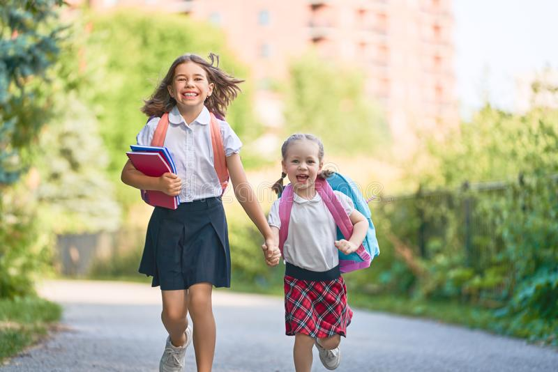 Girls with backpack are going to school stock photography