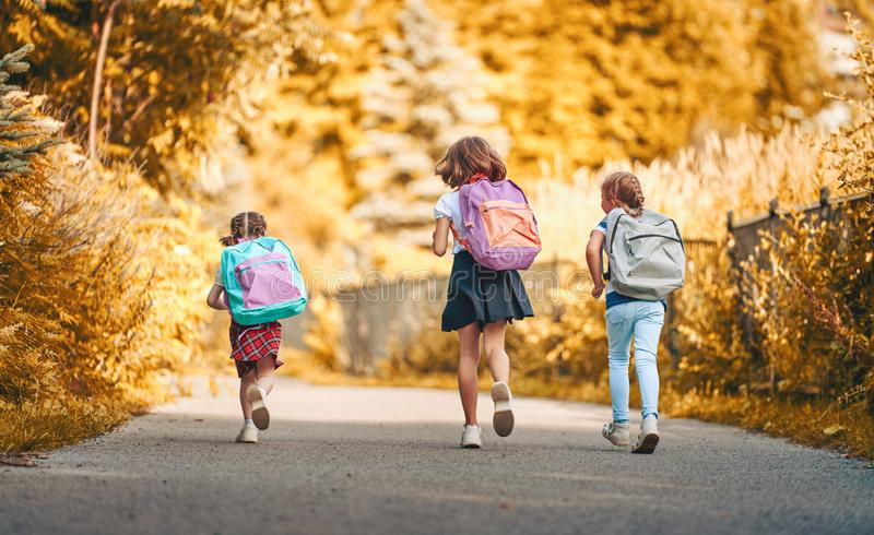 Girls with backpack are going to school royalty free stock photos