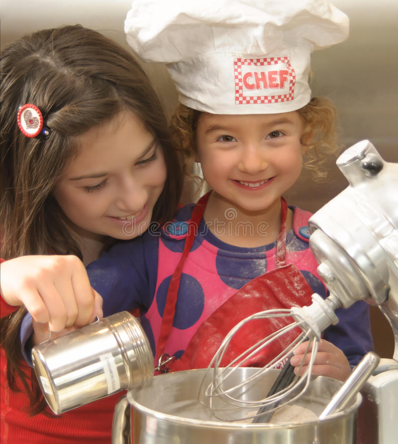 Girls Baking. Older, big sister is holding her younger, little sister's hand and pouring cinnamon sugar into a mixer bowl, helping her sister, who is dressed in
