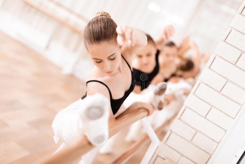 Girls ballet dancers rehearse in ballet class. They are training the stretching. They use ballet barre. They are professional theater actors royalty free stock image
