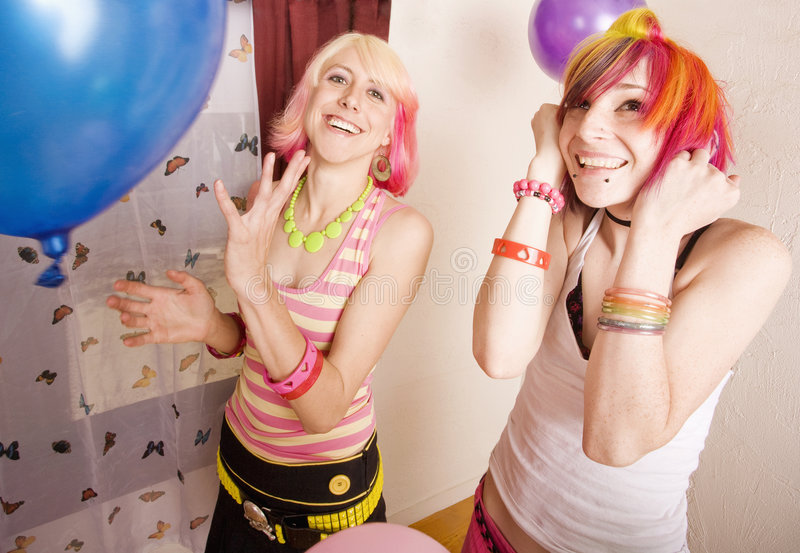 Girls With Balloons. Two punk girls in a room with colorful balloons stock image