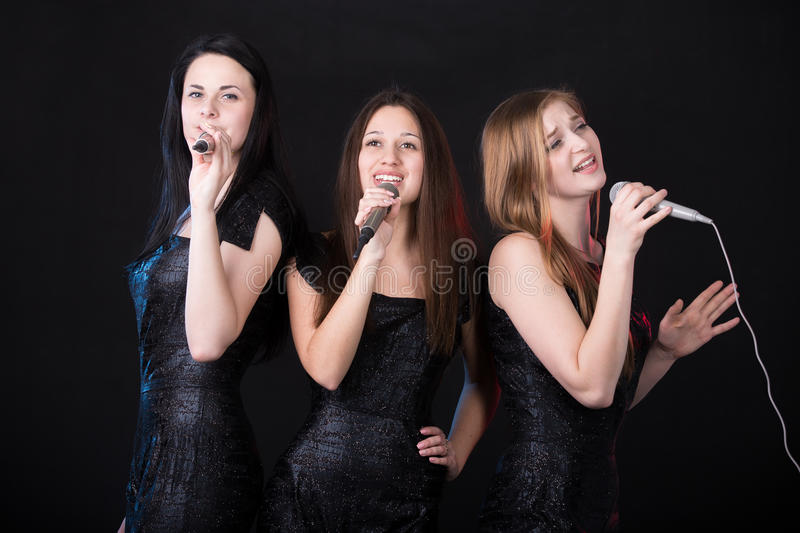 Girls band concert. Group of three emotional beautiful young female singers with microphones singing, girls band concert royalty free stock images
