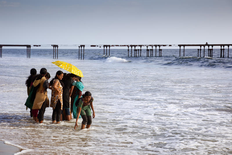 Girls on the beach. Allepey, India-September 6, 2012. Many Indian tourists come to the beach for a walk or swim. One of them wants to touch the water with hers royalty free stock photography