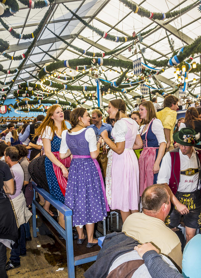 Girls in the beer tent. Girls, dressed in colorful dirndls, are standing on the benches in one of the the big beer tents stock photography