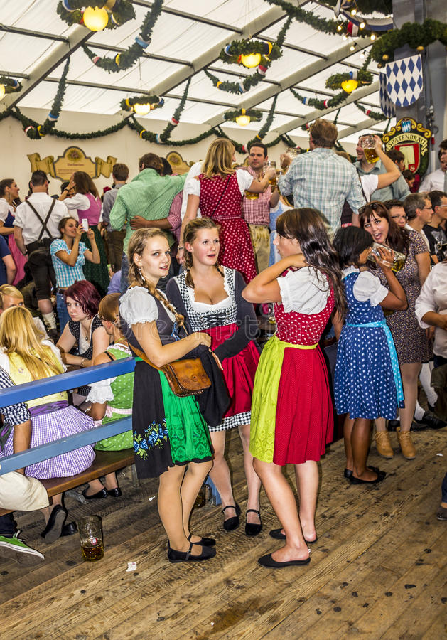 Girls in the beer tent. Girls, dressed in colorful dirndls, are standing together in one of the the big beer tents royalty free stock photography