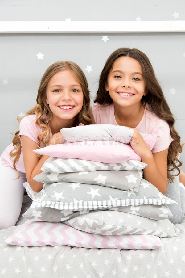 Girls best friends gather in bedroom for slumber party. Domestic party for kids. Girls near pile pillows posing with. Brilliant smiles. Lets start this party royalty free stock photo