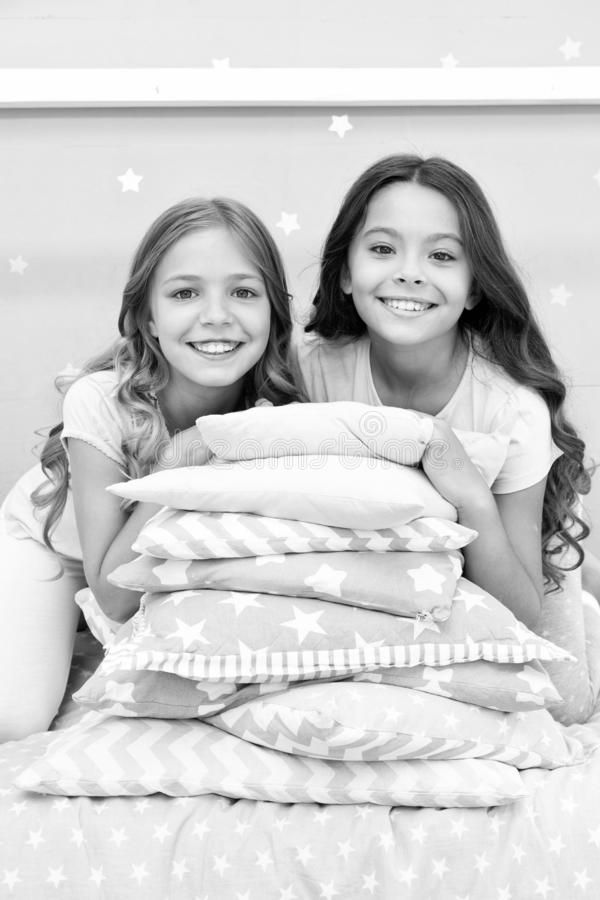 Girls best friends gather in bedroom for slumber party. Domestic party for kids. Girls near pile pillows posing with stock image