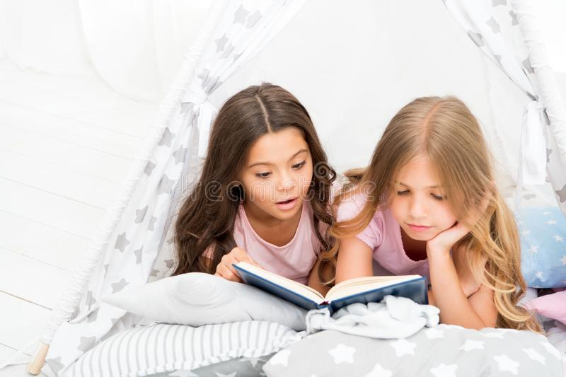 Girls best friends read fairy tale before sleep. Best books for kids. Children read book in bed. Reading before bed can royalty free stock photography