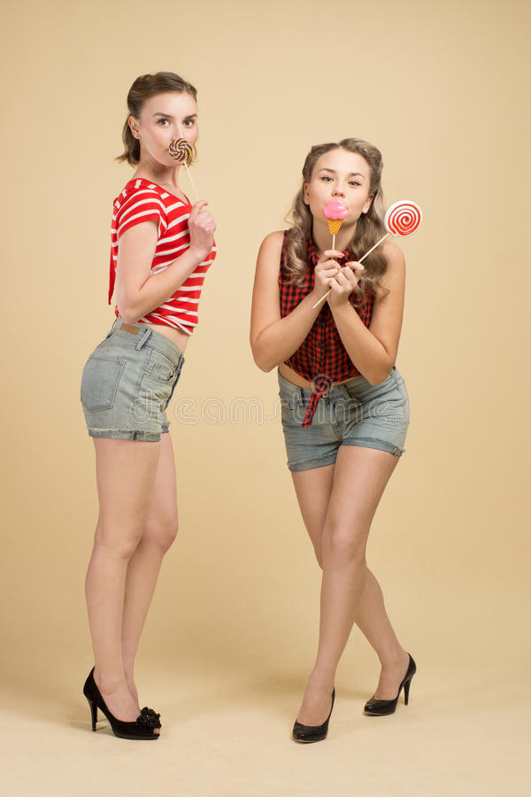 GIRLS WITH BIG CANDYS. Girl in the style of pin - up hold large lollipops stock photos