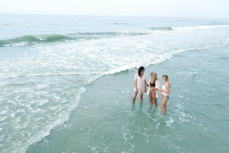 Girls standing in ocean stock photo