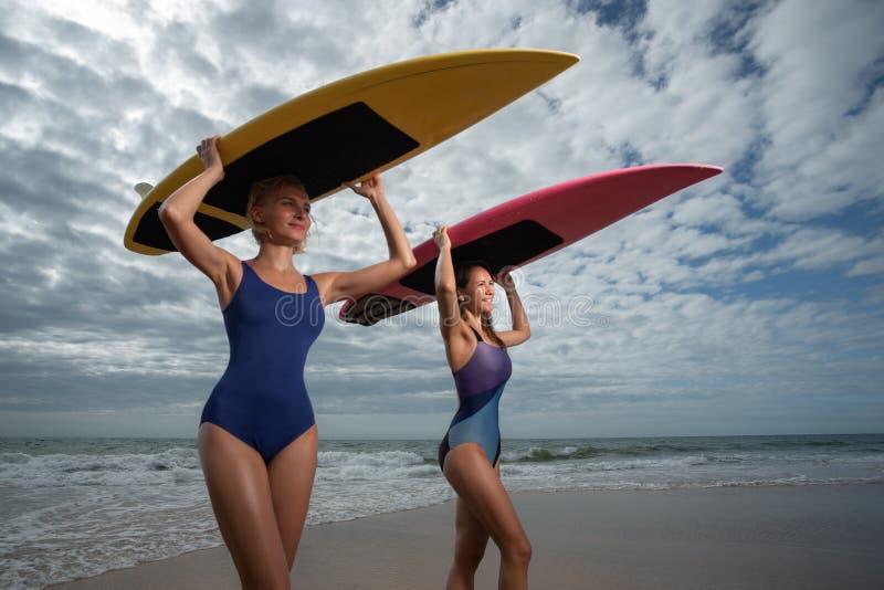 Beautiful young women surfer stock image