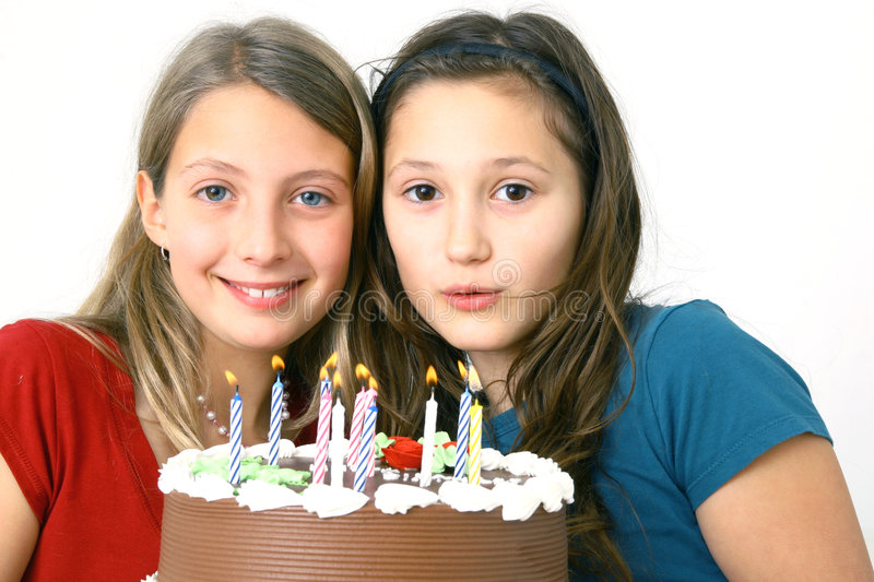 Girls with birthday cake. Two preteens with a chocolate birthday cake royalty free stock photography