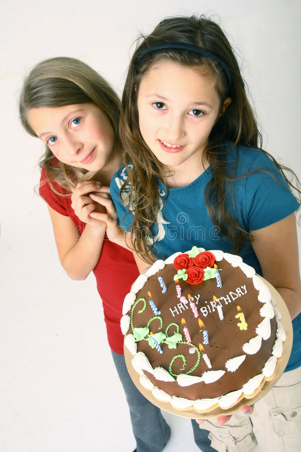Girls with birthday cake. Girls holding a chocolate birthday cake royalty free stock images