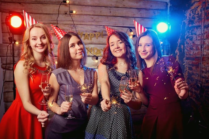 Girls for birthday party in the caps on their heads and with sparklers their hands.  stock photos
