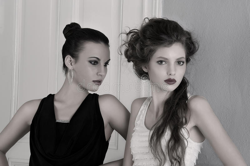 Girls in black and white dresses with amazing. Two beautiful girls with amazing styles and elegant dresses posing indoor near an old fashion door posing with stock photography