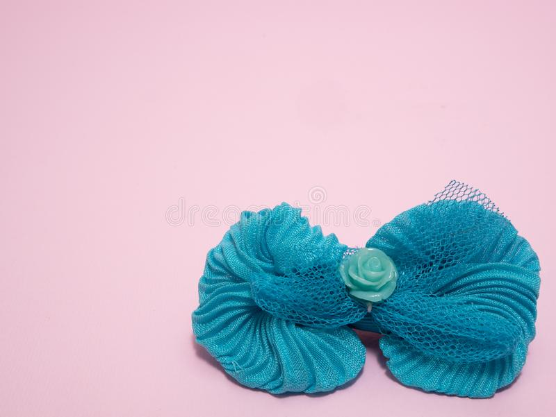 Girls blue hair tie bow on pink background royalty free stock images