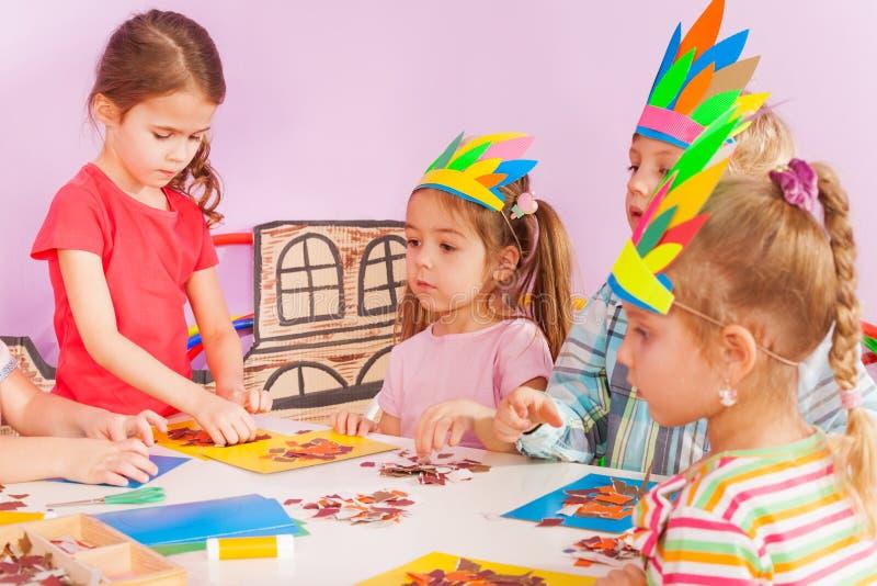 Girls and boy in kindergarten craft class gluing. Handmade postcard wearing cardboard headdress royalty free stock image