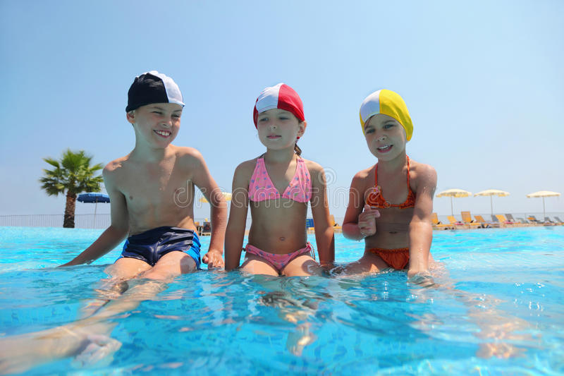 Girls and boy sit on skirting in pool and speak stock photos