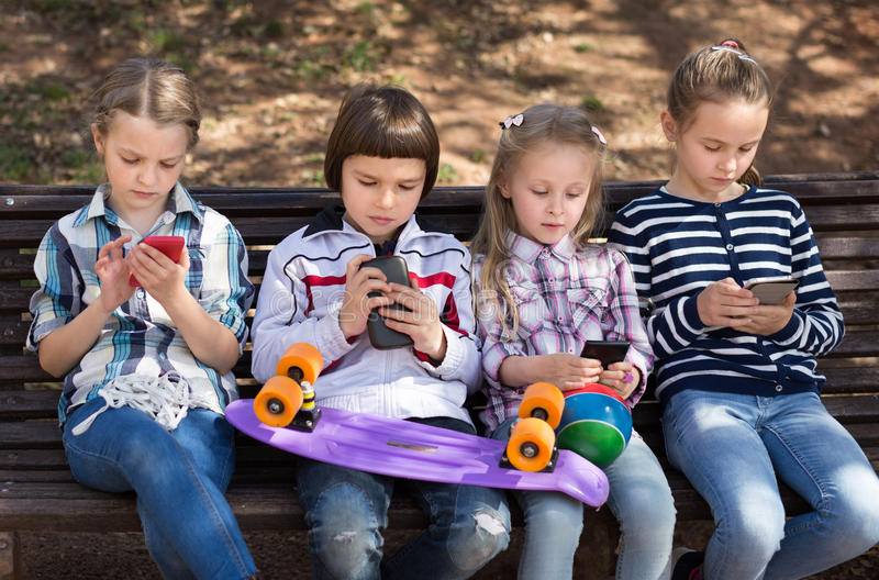 Girls and boy with smartphones on bench in park in autumn stock photos
