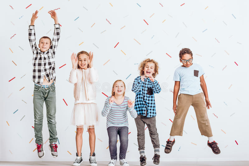 Girls and boys jumping. Happy girls and boys jumping in a room stock photo