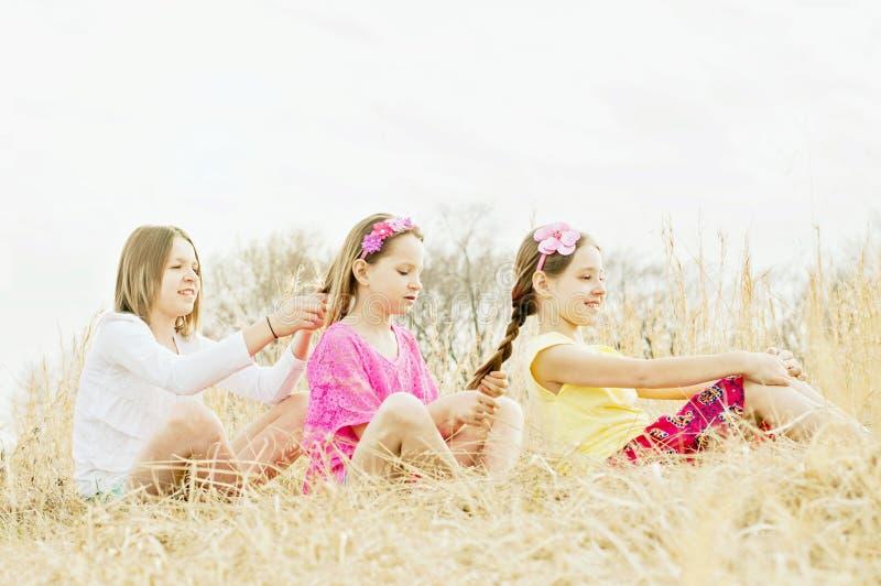 Girls braiding hair in country meadow. Three sisters sit in country meadow and braid each other's hair