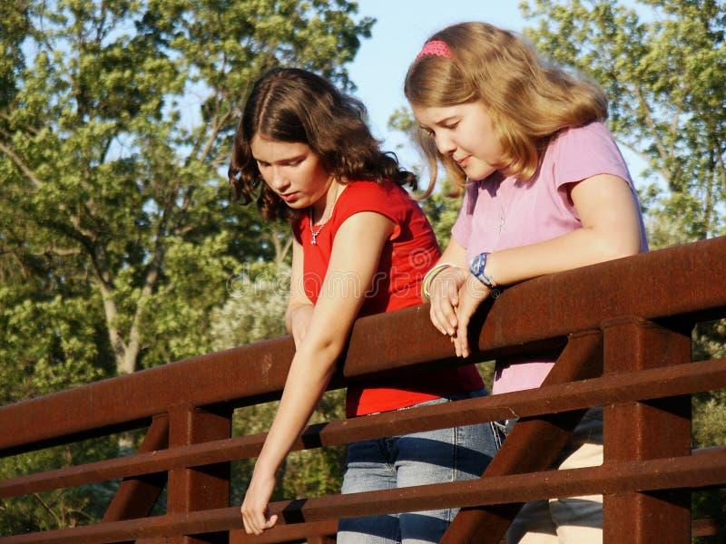 Girls on bridge. Looking at object below royalty free stock image