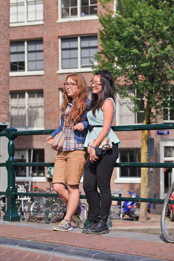 Girls on a bridge in the ancient canal belt, Amsterdam, netherlands. AMSTERDAM-AUG. 27, 2014. Two girls pose on a bridge in canal belt. Amsterdam is the most royalty free stock photos