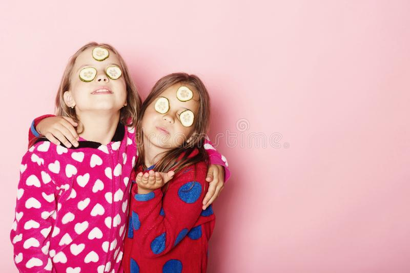 Girls in bright pink pajamas hug. Kids on pink background. Girls in bright pink pajamas hug. Kids pose on pink background sending kisses, copy space. Children royalty free stock image