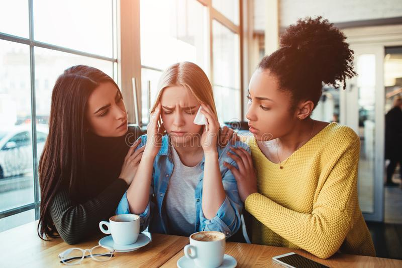 Girls in cafe. One more picture of sad girls where two of them are trying to support mentally their friend. She is crying beause of the fact she is preganat and stock photo