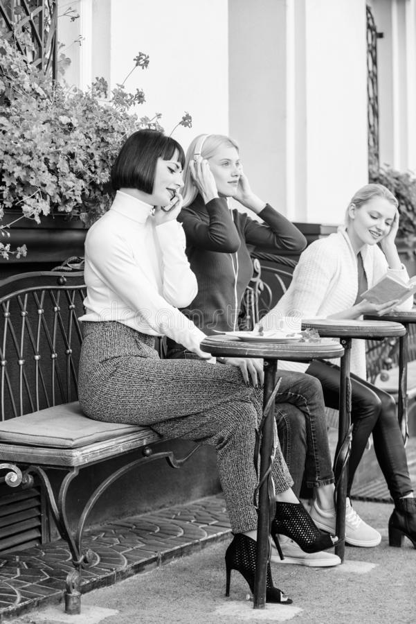 Girls in cafe. social diversity. listening music. reading book. speaking on phone. frienship. free time spending. relax royalty free stock images