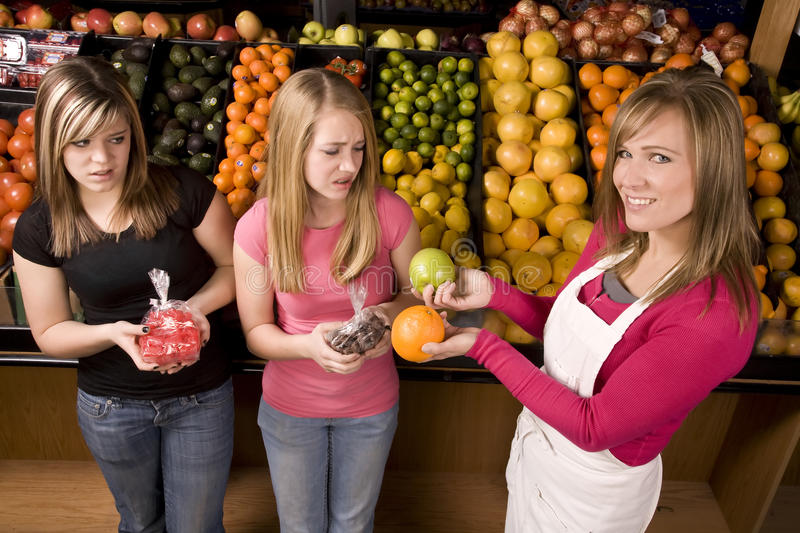 Girls candy fruit. Two teen girls not wanting to take the orange from the worker, they would rather have the candy stock images