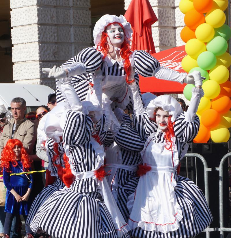 Girls at carnival masked in dolls, posed in dance choreography on a beautiful sunny day royalty free stock photos
