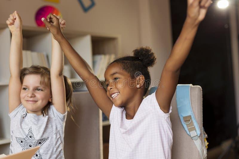 Girls celebrating finishing homework stock image