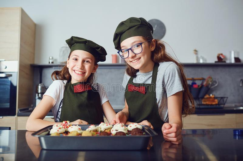 Girls children in cook uniforms in the kitchen. royalty free stock photos