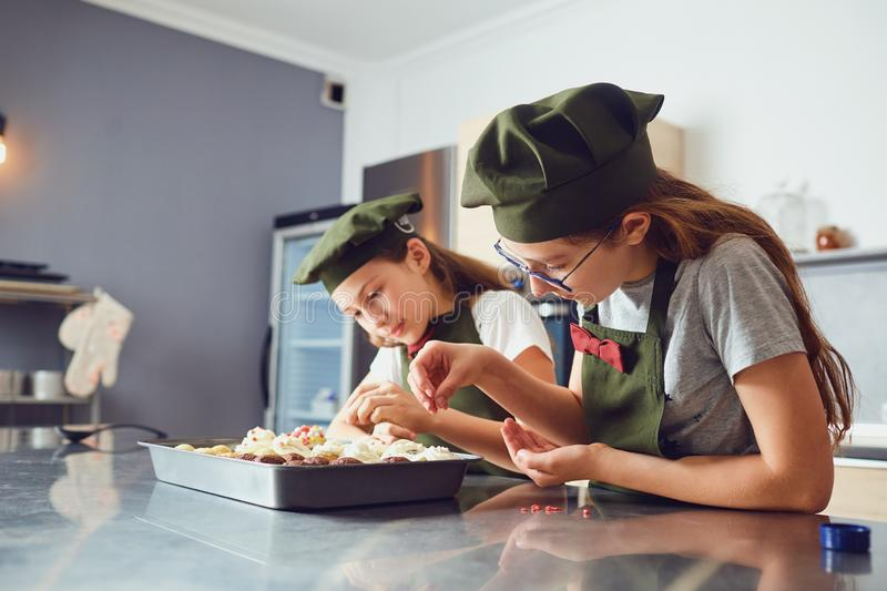 Girls children in cook uniforms in the kitchen. royalty free stock images