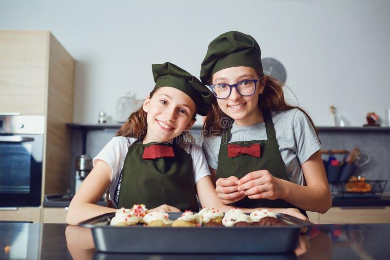 Girls children in cook uniforms in the kitchen. stock photos