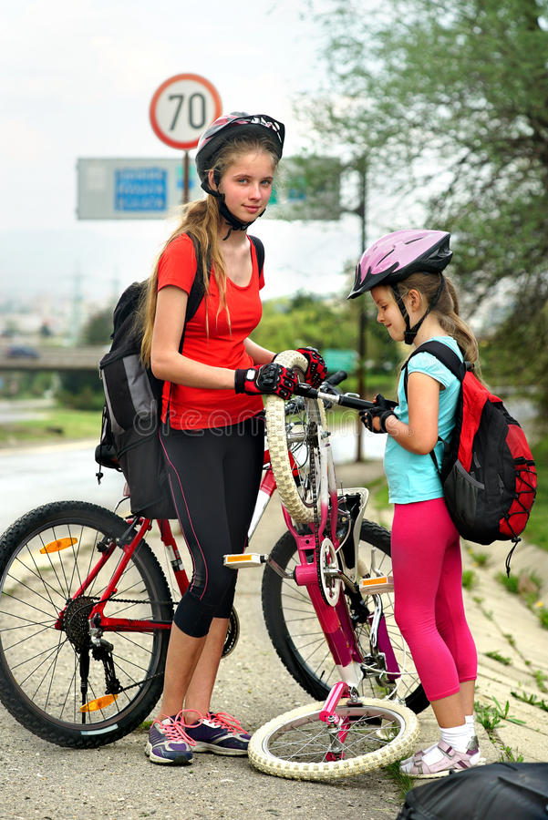 Girls children cycling Family pump up bicycle tire. Bikes bicyclist girl. Child girls wearing bicycle helmet with hand pump for bicycle. Girl pump up bicycle stock image