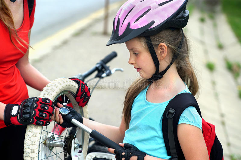 Girls children cycling Family pump up bicycle tire. Bikes bicyclist girl. Family wearing bicycle helmet with hand pump for bicycle. Girl child pump up bicycle stock image