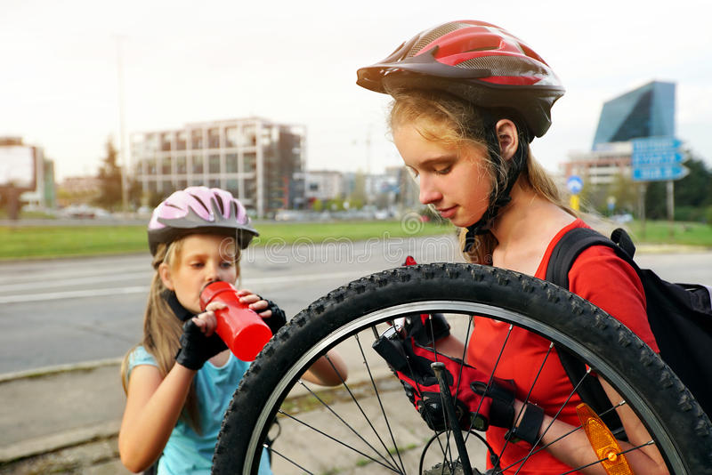Girls children cycling Family pump up bicycle tire. Bicycle tire pumping by child bicyclist . Kid wearing bicycle helmet with hand pump for bicycle. Girl drink stock photo
