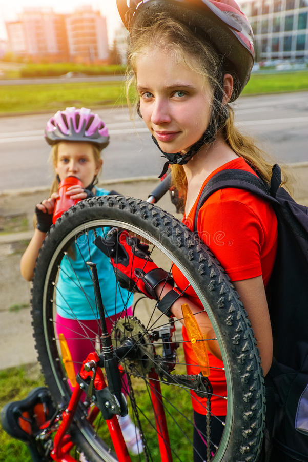 Girls children cycling Family pump up bicycle tire. Bicycle tire pumping by child bicyclist. Kid wearing bicycle helmet with hand pump for bicycle. Girl drink stock images