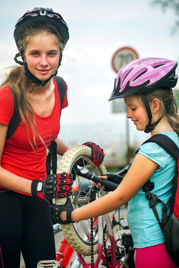 Girls children cycling Family pump up bicycle tire. stock photography
