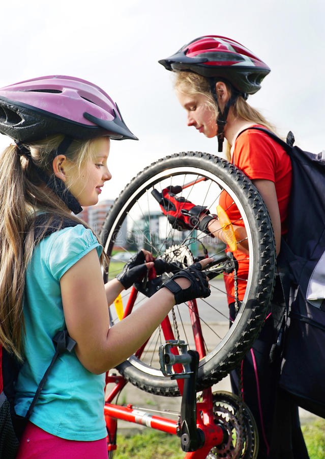 Girls children cycling pump up bicycle tire. royalty free stock images